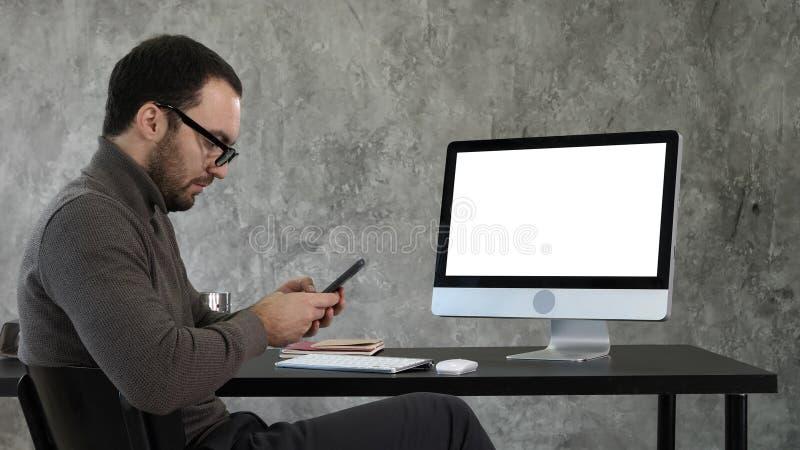 Biznesmen patrzeje jego smartphone obsiadanie i przesyłanie wiadomości blisko ekranu komputerowego Biały pokaz fotografia stock