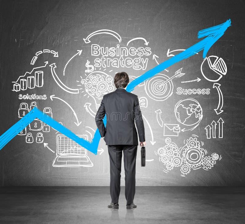 Biznesmen patrzeje narastającego błękitnego wykres z walizką i strategia biznesowa kreślimy zdjęcie stock
