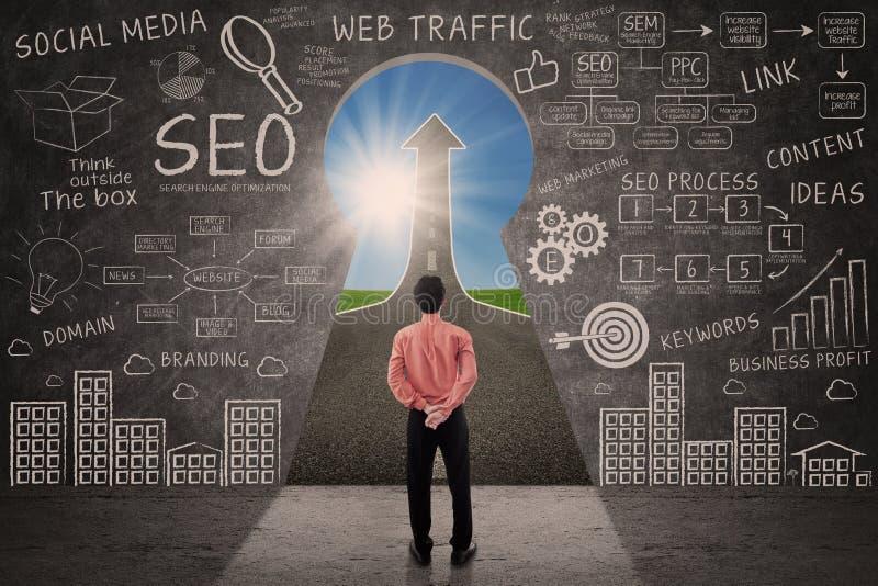 Biznesmen patrzeje przez kluczowej dziury z SEO doodle na blackboard