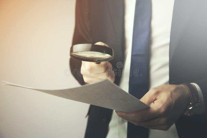 Biznesmen patrzeje przez powiększać dokumenty - szkło zdjęcie stock