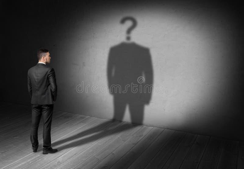 Biznesmen patrzeje znaka zapytania zamiast głowy jego cień zdjęcie stock