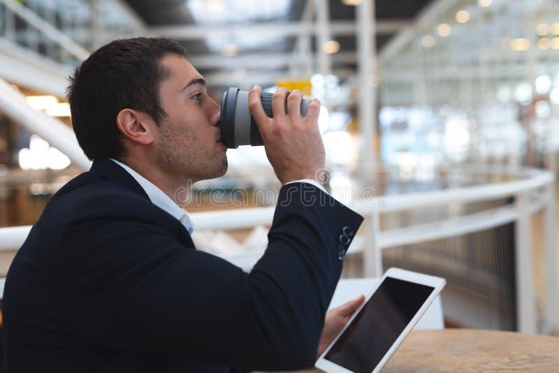 Biznesmen pije kawę podczas gdy pracujący na cyfrowej pastylce przy stołem w nowożytnym biurze fotografia stock
