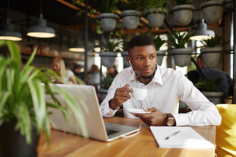 Biznesmen pije kawę w cukierniany odpoczywać po pracy z laptopem zdjęcia stock