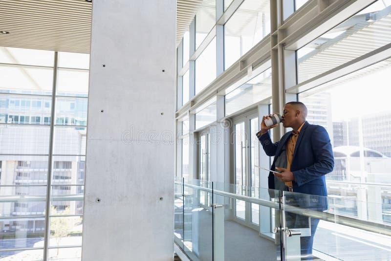 Biznesmen pije kawową pozycję w nowożytnym budynku biurowym zdjęcia stock