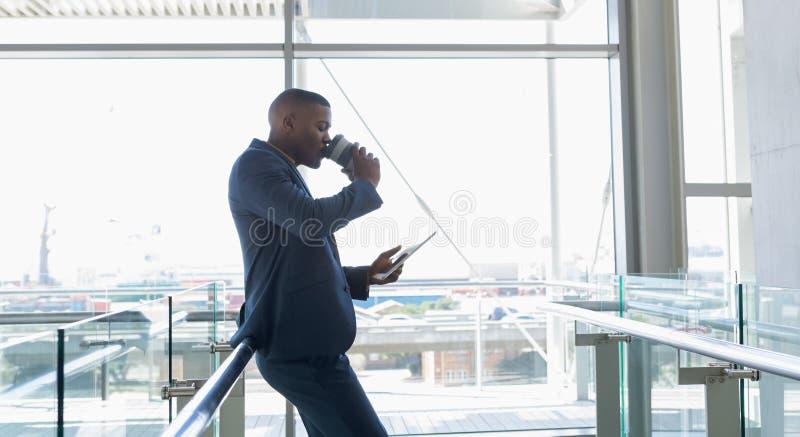 Biznesmen pije kawową pozycję w nowożytnym budynku biurowym fotografia stock