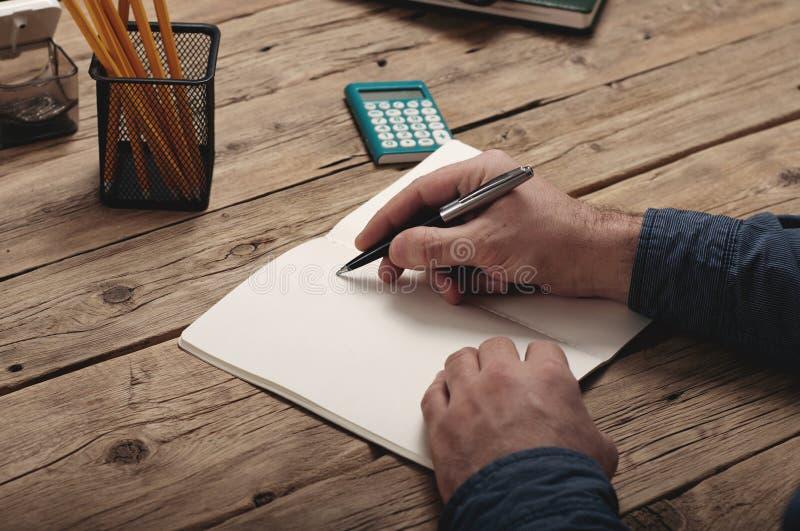 Biznesmen pisze notatnik na drewnianym stole obraz royalty free
