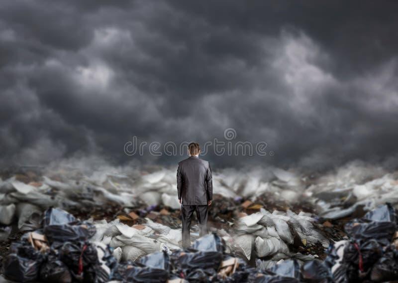 Biznesmen po środku śmieci, tylny widok zdjęcie stock