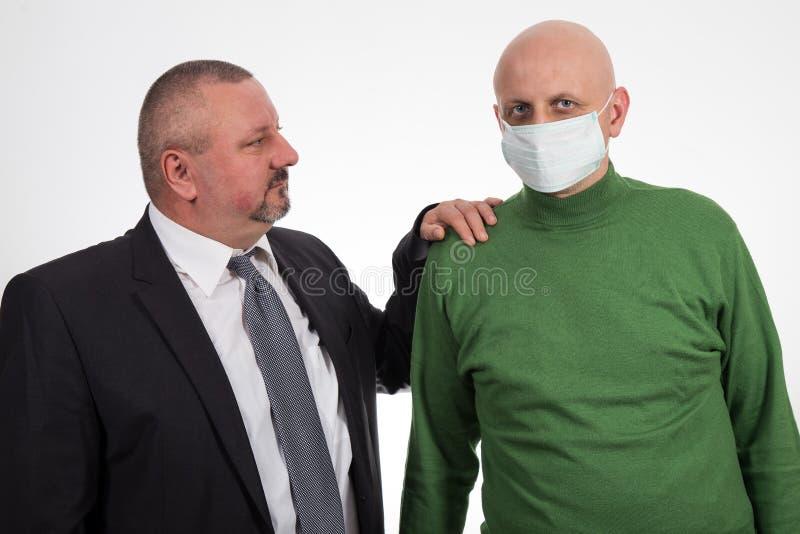 Biznesmen pociesza młodego człowieka cierpienie od nowotworu zdjęcia royalty free
