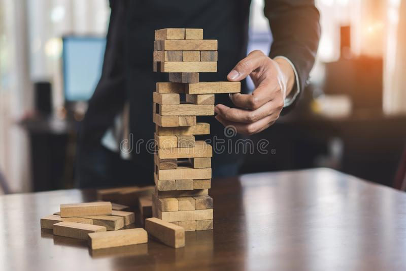 Biznesmen podnosi drewniany blokowego nie udać się niebezpieczeństwa wierza obraz stock