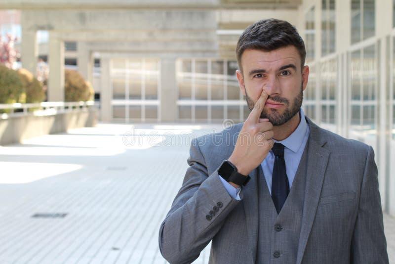 Biznesmen podnosi jego nos w powierzchni biurowa zdjęcie stock
