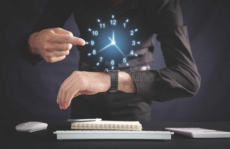 Biznesmen pokazujący zegar w biurze Zarządzanie czasem pracy obrazy stock