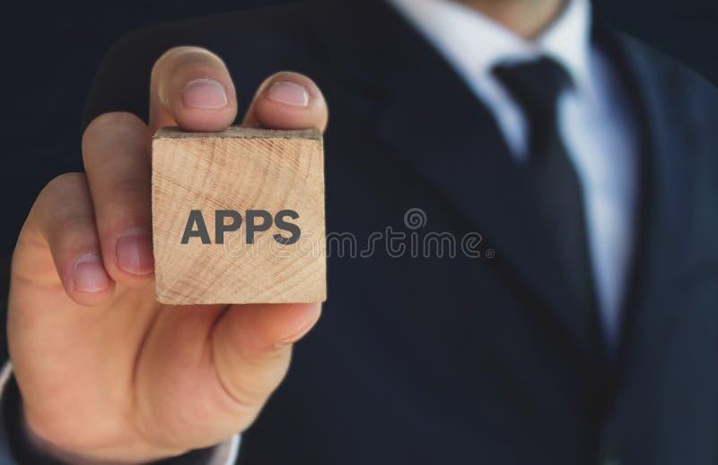 Biznesmen pokazuje APPS słowo w drewnianym sześcianie obraz stock