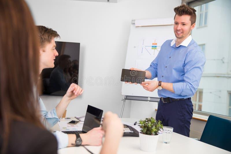 Biznesmen pokazuje cyfrową pastylkę koledzy obraz royalty free