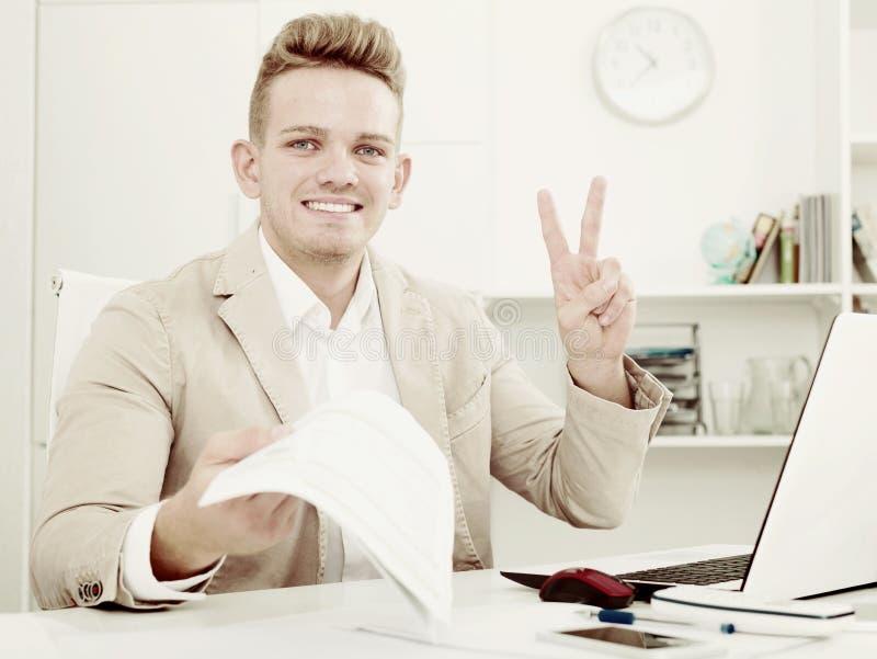Biznesmen pokazuje zwycięstwo podpisuje wewnątrz biuro obrazy stock
