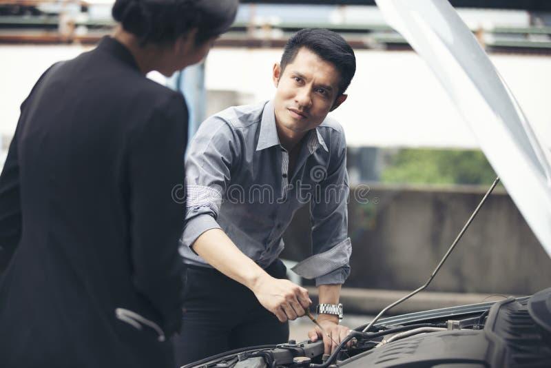 Biznesmen pomocy bizneswomany sprawdzają łamanych samochody i naprawiają zdjęcie stock