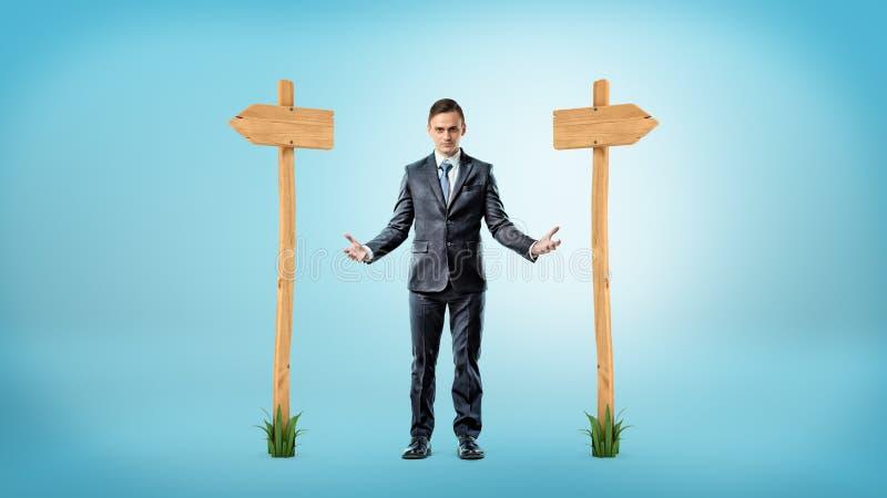Biznesmen pozycja między dwa drewnianymi znakami wskazuje różni kierunki zdjęcie stock