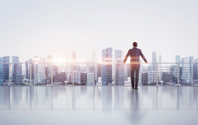 Biznesmen pozycja na dachu i patrzeć obraz royalty free