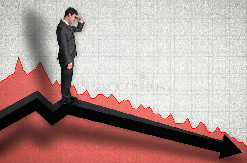 Biznesmen pozycja na wykresie i patrzeć w dół na rezultatach zdjęcie stock