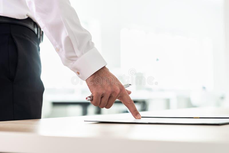 Biznesmen pozycja przy jego biurkiem wskazuje dokument, zastosowanie lub kontrakt trzyma pióro, zdjęcia stock