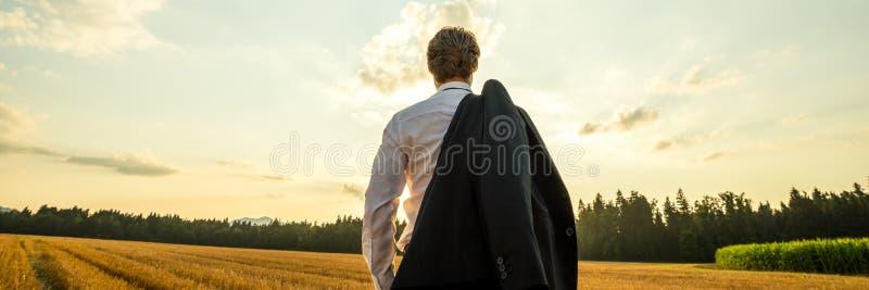 Biznesmen pozycja w naturze pod wieczór niebem patrzeje wewnątrz odległość z jego kostium kurtką nad jego obrazy stock