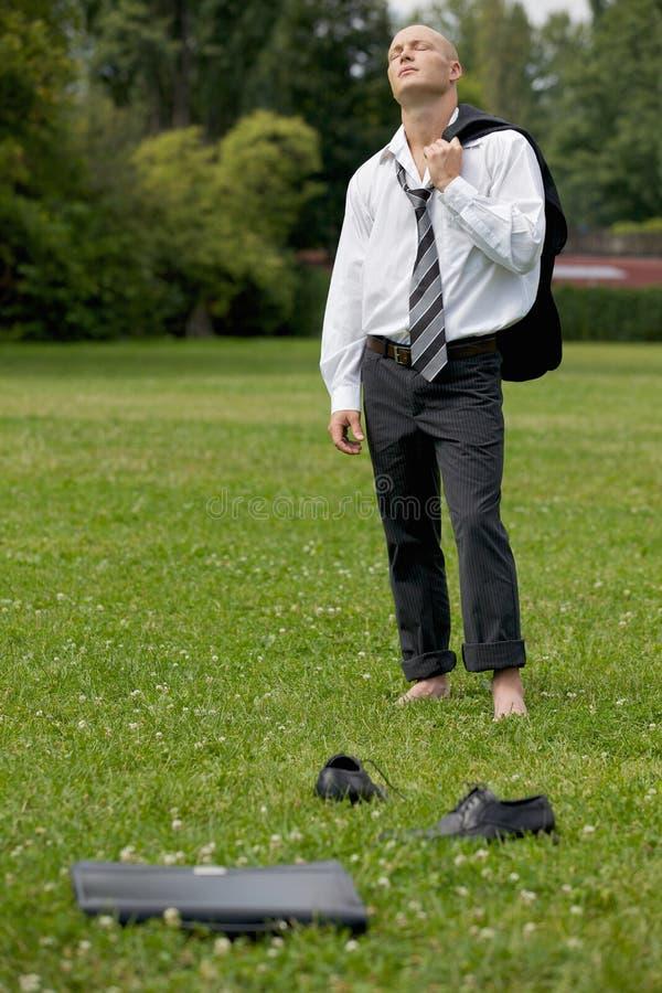 Biznesmen pozycja w parku, oczy zamykający zdjęcie royalty free