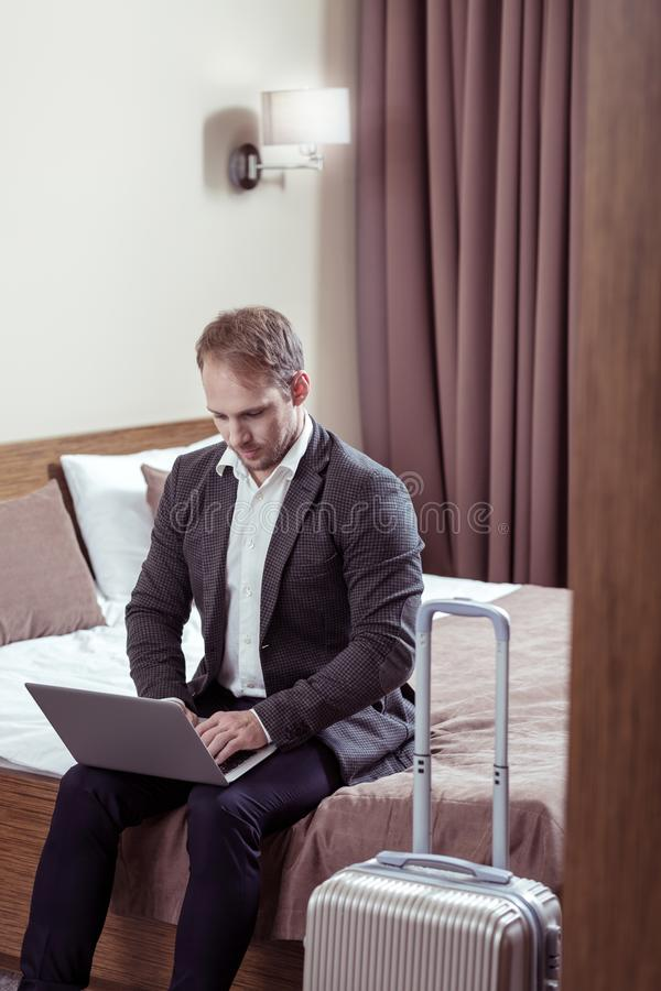 Biznesmen pracuje na jego laptopie przed opuszczać pokój hotelowego zdjęcia stock