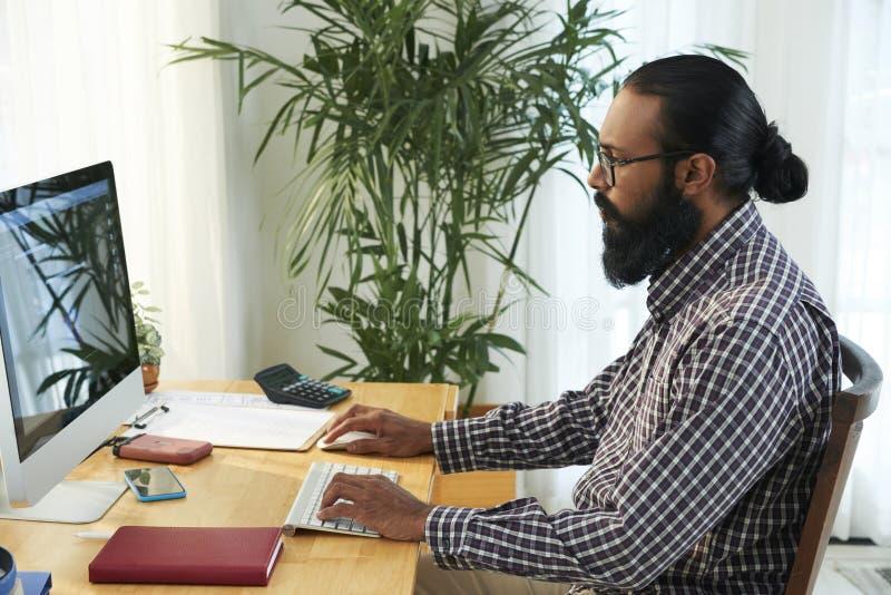 Biznesmen pracuje na komputerze przy biurem zdjęcia stock