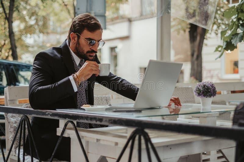 Biznesmen pracuje na laptopie i pije kawę obraz royalty free