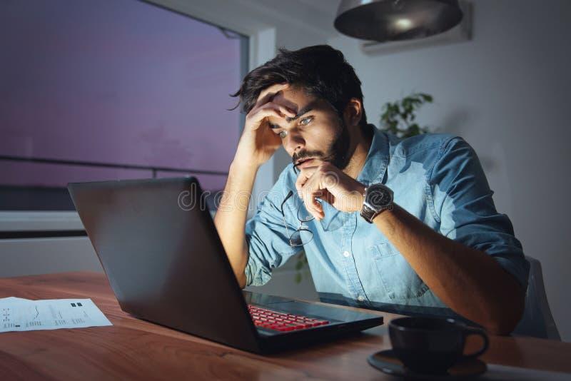 Biznesmen pracuje na laptopie, przepracowywać się, w stresie fotografia stock