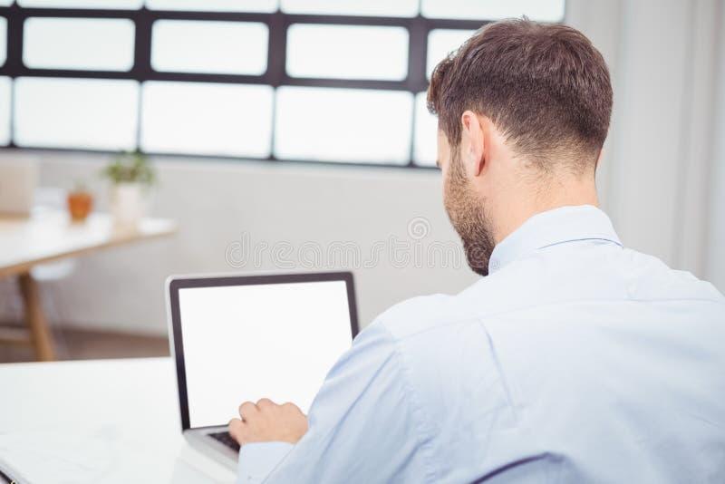 Biznesmen pracuje na laptopie przy biurkiem w biurze obrazy stock