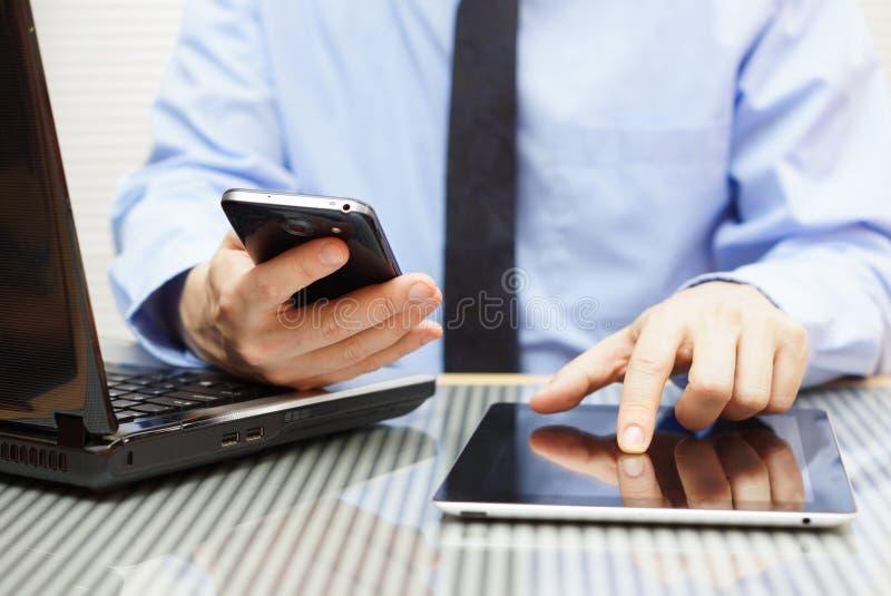 Biznesmen pracuje na pastylce i używa mądrze telefon zdjęcia stock