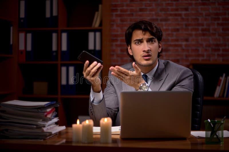 Biznesmen pracuje póżno w biurze z świeczki światłem zdjęcia stock