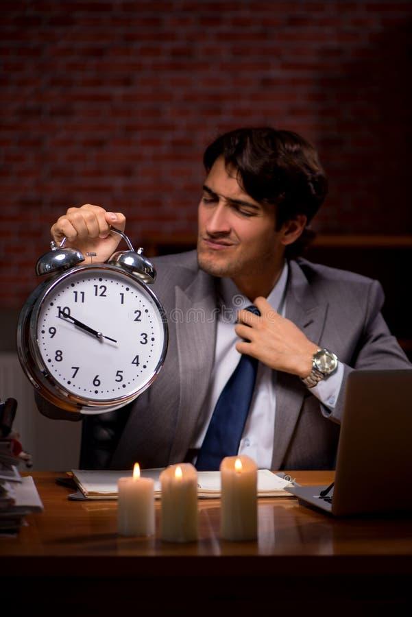 Biznesmen pracuje póżno w biurze z świeczki światłem obrazy stock