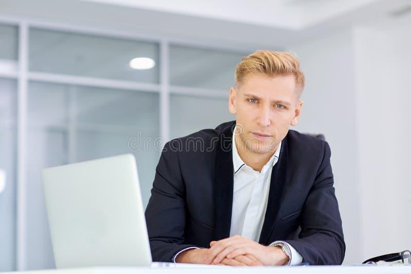 Biznesmen pracuje przy jego biurkiem z laptopem w biurze fotografia royalty free