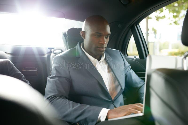 Biznesmen pracuje wśrodku samochodu podczas gdy podróżujący obraz royalty free