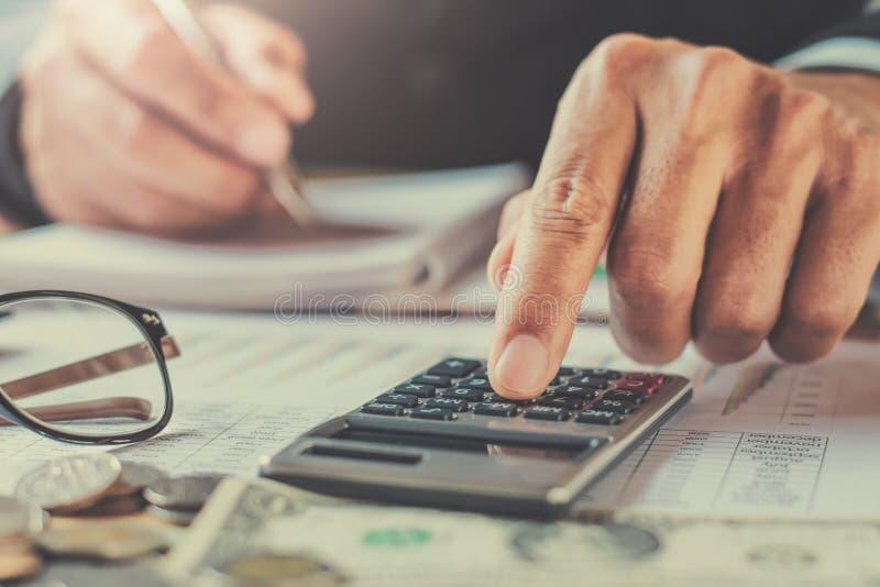 biznesmen pracuje w biurowym używa kalkulatorze kalkulować budg zdjęcie royalty free
