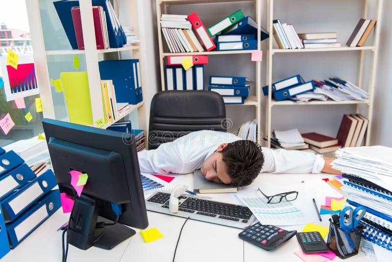 Biznesmen pracuje w biurze z stosami książki i papiery obraz stock