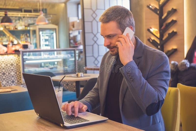 Biznesmen pracuje w laptopie i opowiada na telefonie komórkowym w kawiarni zdjęcie stock