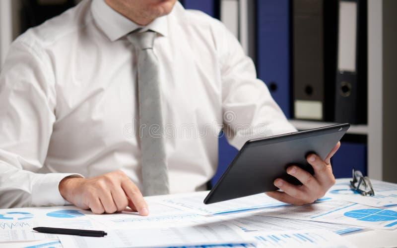 Biznesmen pracuje z pastylka komputerem osobistym i pisze raportach, cyrklowanie, czytanie Biurowy pracownik, stołowy zbliżenie b zdjęcie stock
