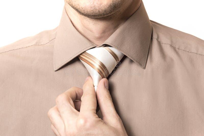Biznesmen prostuje jego krawata zbliżenie na białym tle zdjęcie stock