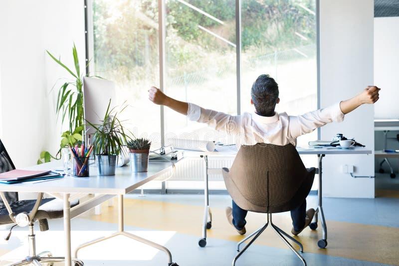 Biznesmen przy biurkiem w jego biurowych rozciąganie rękach zdjęcie stock