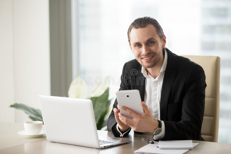 Biznesmen przy biurowym biurkiem używać komputerową pastylkę fotografia stock
