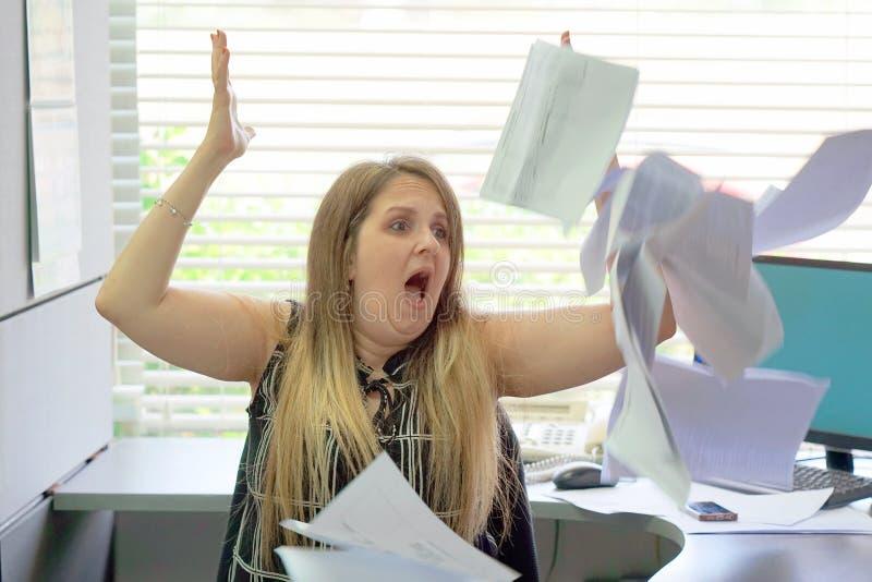 Biznesmen przy jego biurko rzutów papierami w powietrze i dokumentami zdjęcia stock