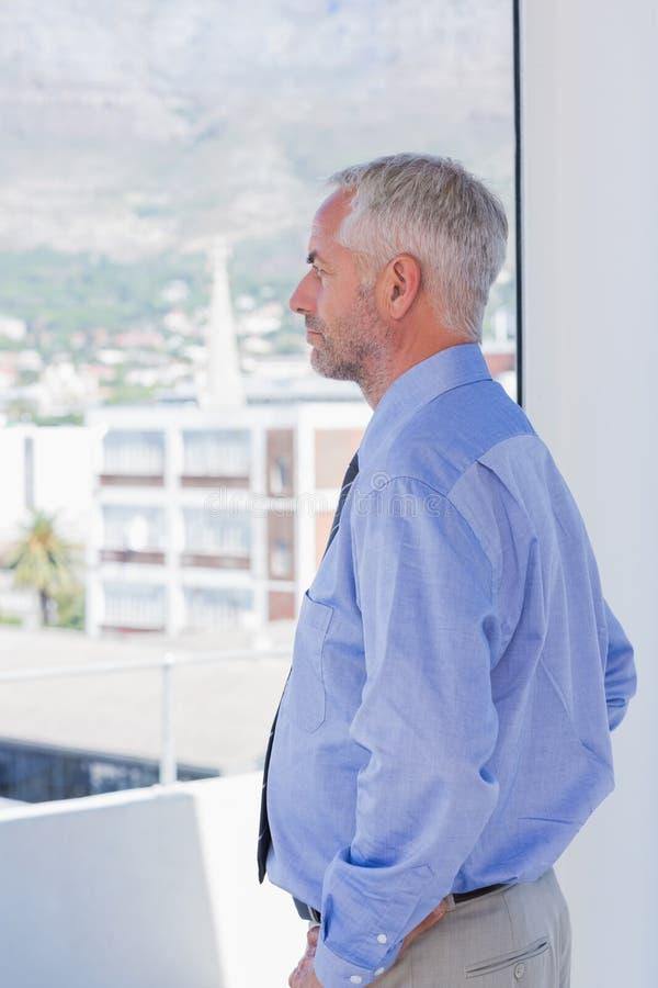 Biznesmen przyglądający out okno obraz stock