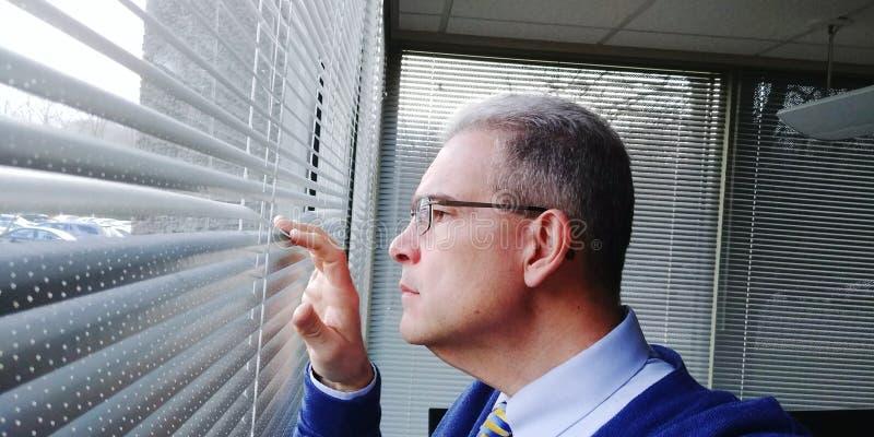 Biznesmen przyglądający za okno jego biuro zdjęcie stock
