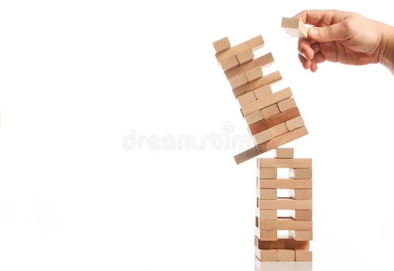 Biznesmen ręka bierze jeden blok od wierza obrazy stock