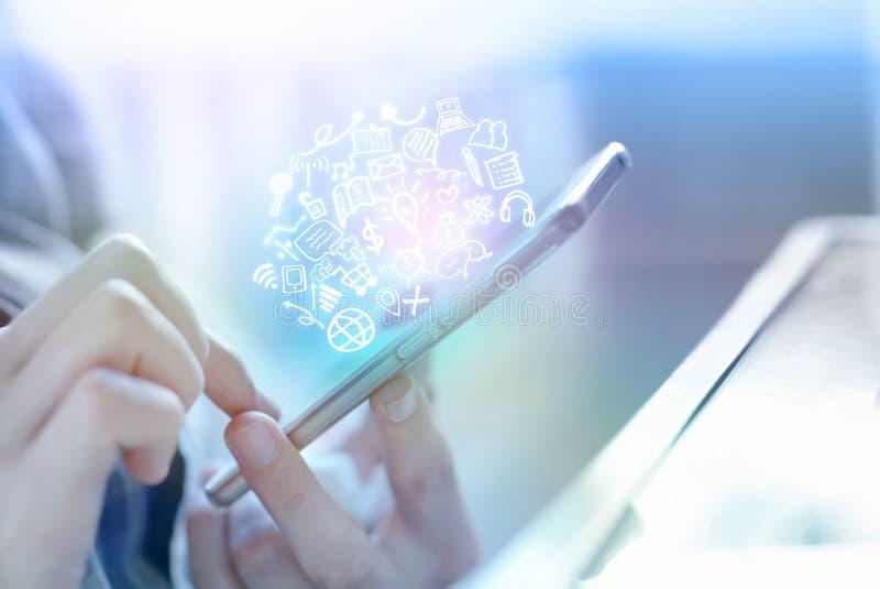 Biznesmen ręka trzyma mądrze telefon łączy interneta i socjalny środków ikony zdjęcia stock
