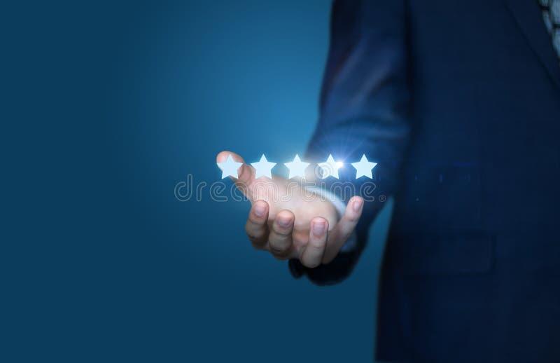 Biznesmen ręka trzyma pięć gwiazd odizolowywający zdjęcia royalty free
