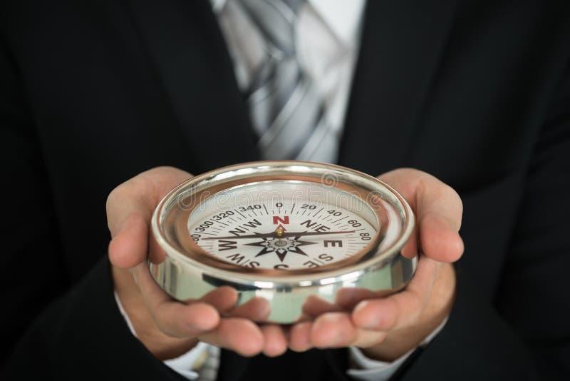 Biznesmen ręki mienia kompas zdjęcia stock