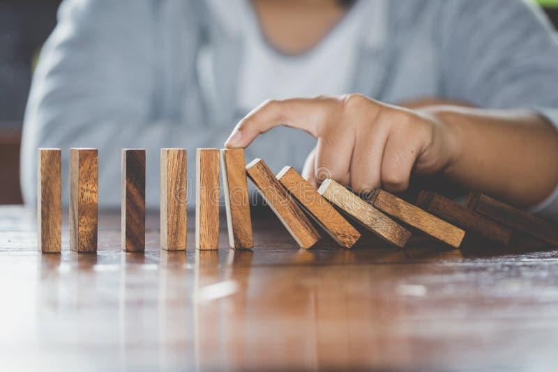 Biznesmen ręki powstrzymywania domin spada drewniany skutek od c obraz royalty free